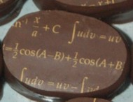 chocolates with mathematical expressions in gold lettering